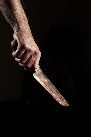 cuchillo: Hombre con cuchillo ensangrentado, la mano cerca, fondo oscuro Foto de archivo