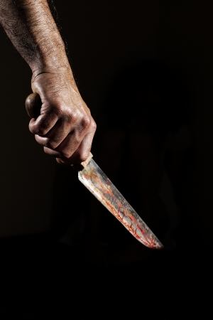bloody: Man with bloody knife, hand close up, dark background