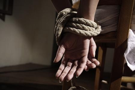 gefesselt: Junge Frau auf einem Stuhl in einem leeren Raum gebunden, schlie�en Sie die H�nde hoch Lizenzfreie Bilder