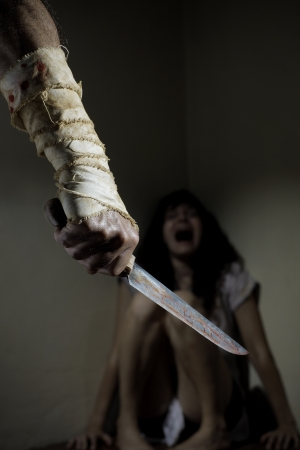 Scared woman threatened by a man with bloody knife photo