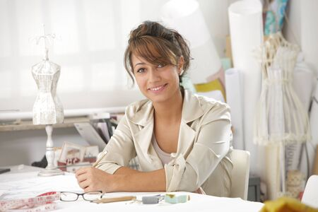 Smiling female fashion designer sitting at office desk photo