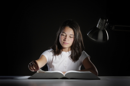 night school: Young girl student, studying late into the night with her book and homework  Stock Photo
