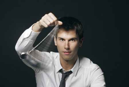 hypnosis: Businessman holding a pocket watch and swinging it in the fashion of a hypnotist