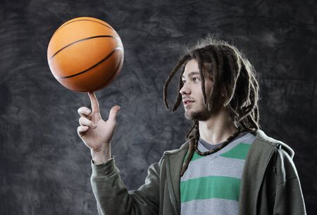 Portrait of young man spinning basketball on finger photo