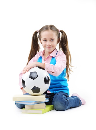 Cute little girl with books and soccer ball on white background photo