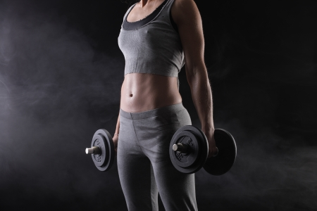 weight training: Fitness woman with weights on dark background