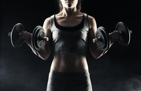 levantar peso: Mujer joven levantando las pesas