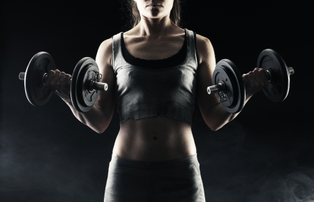 body building: Young woman lifting the dumbbells
