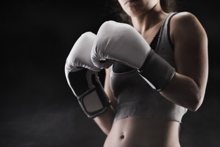 builds: Woman boxer, focus on boxing glove, shallow deep of field Stock Photo