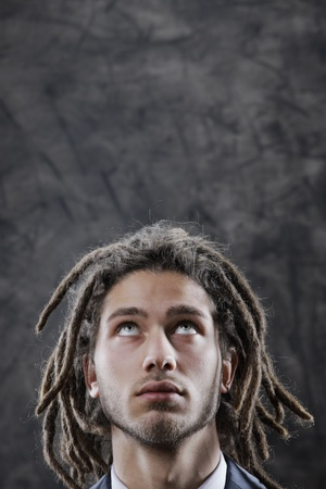 dreadlock: Young man looking up at copy space