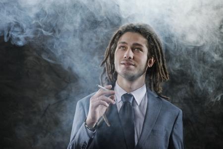 smoking marijuana: Rastafarian businessman smoking marijuana