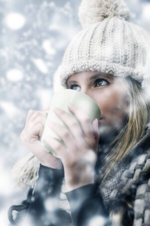 Young woman wearing winter clothes having a hot drink  photo