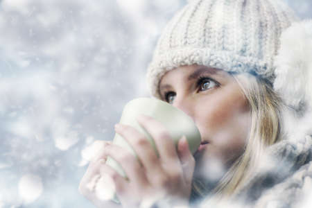 Young woman wearing winter clothes having a hot drink Stock Photo - 17408778