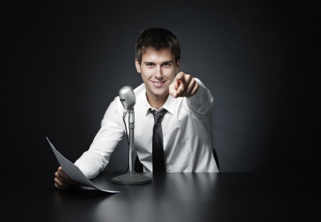 journalist: Anchorman smiling pointing at you  Stock Photo