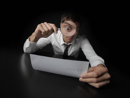 Young businessman looking to a contract through a magnifying glass  photo