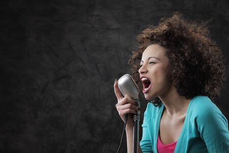 female singer: Young female singer with brown curly hair singing a song  Stock Photo