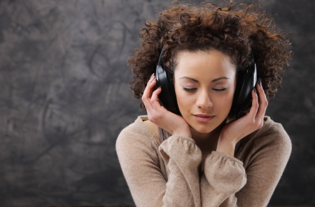 individuality: Young beautiful woman listening to music with headphones