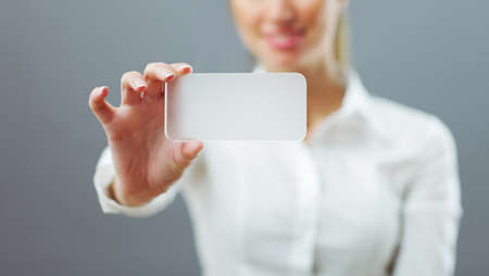 Businesswoman showing her business card. Shallow depth of field - focus on fingers and card. You can just add your text there. Stock Photo - 17625607