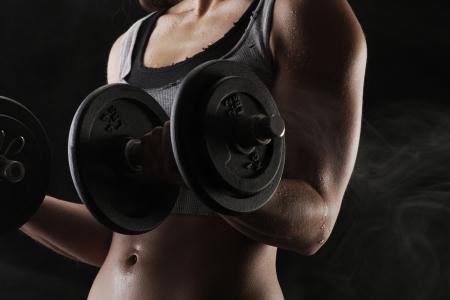pesas: Mujer joven levantando las pesas