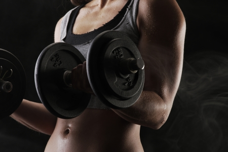 recreational sport: Young woman lifting the dumbbells