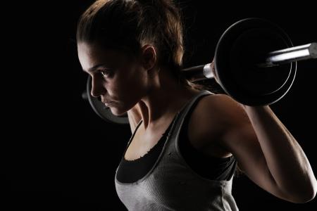 levantando pesas: Joven mujer levantando pesas Foto de archivo