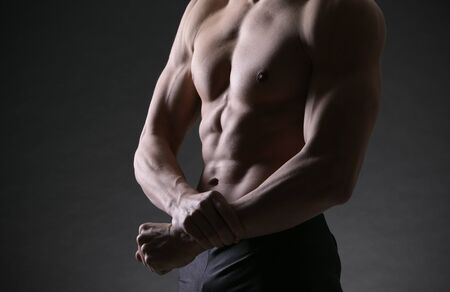 A shirtless male of a healthy fit young guy flexing his biceps Stock Photo - 17799637