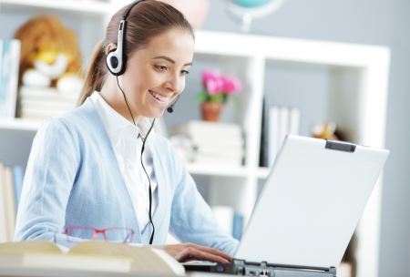 Young girl chating on laptop with headset Stock Photo