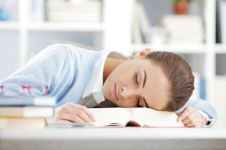 cansancio: mujer estudiante durmiendo en el libro Foto de archivo