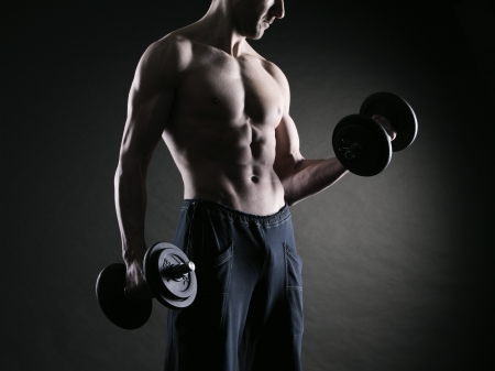 Muscular male athlete is training by lifting dumbbells Stock Photo - 17799639