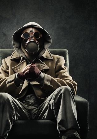 danger: L'uomo in maschera antigas seduto su una sedia Archivio Fotografico