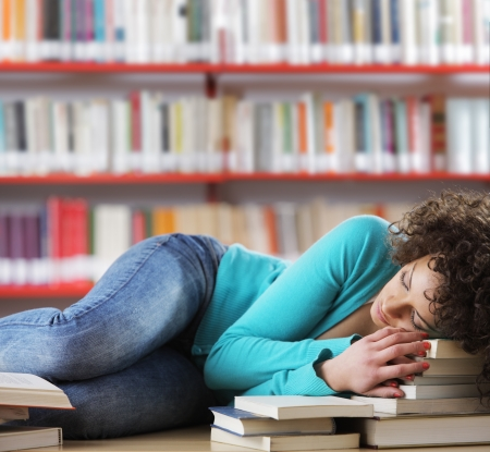 Student sleeping on desk in the library Stock Photo - 17799974