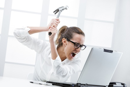 computer problems: Fuori di testa donna d'affari con un martello pronto a distruggere il suo computer portatile Archivio Fotografico