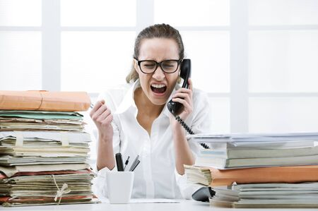 freaked: Young business woman shouting to handset phone Stock Photo