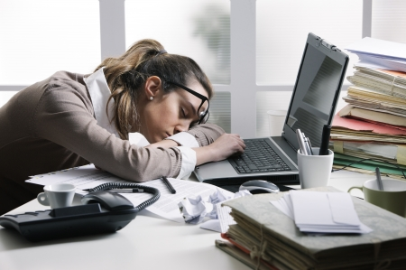 tired worker: Tired businesswoman sleeping on the desk, in front of the computer screen.