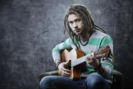 a guitarist boy playing guitar: Young man playing acoustic guitar