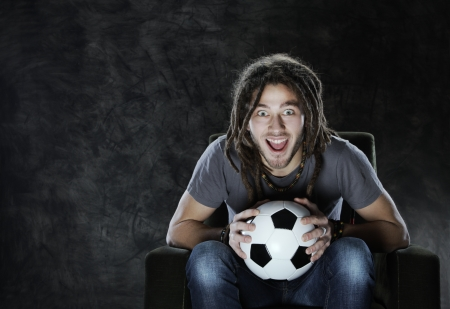 supporter: Young adult man exults watching football on television: Goal! Stock Photo