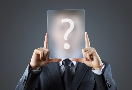 people from behind: Young business man holding question mark signs in front of his faces Stock Photo