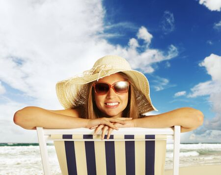 Beautiful young woman relaxing on beach chair photo