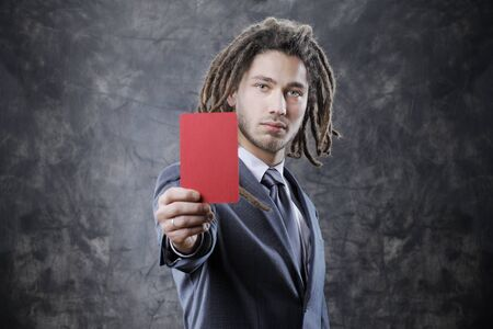 assigning: Businessman referee assigning a red card