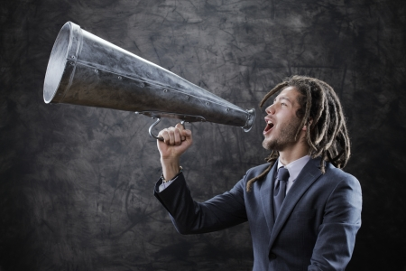 trough: Young businessman yelling trough a vintage megaphone