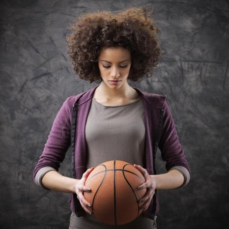 baloncesto chica: Retrato de una mujer hermosa joven que sostiene una pelota de baloncesto