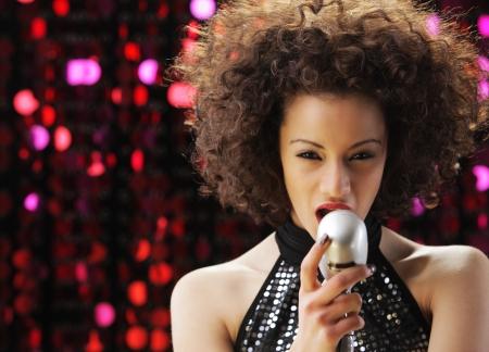 persona cantando: Joven cantante femenina con el pelo marr�n rizado cantar una canci�n