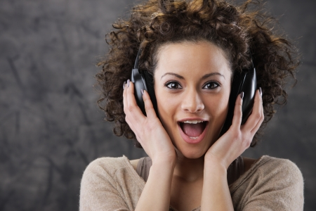 african fashion: Happy woman listening to music with headphones Stock Photo