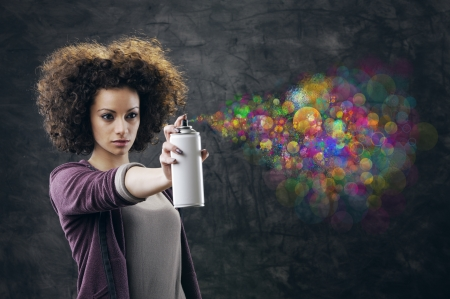 Beautiful girl about to draw a graffiti on a wall with copyspace