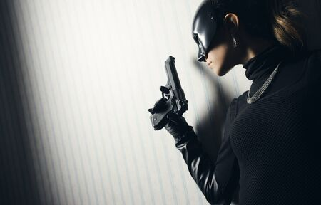 women with guns: Female thief in black mask with gun