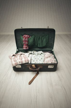 Vintage suitcase open on a wood floor in an empty room Stock Photo - 18096922