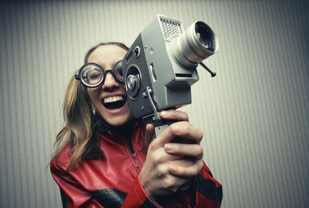 mad girl: Nerdy woman using old fashioned cine camera Stock Photo