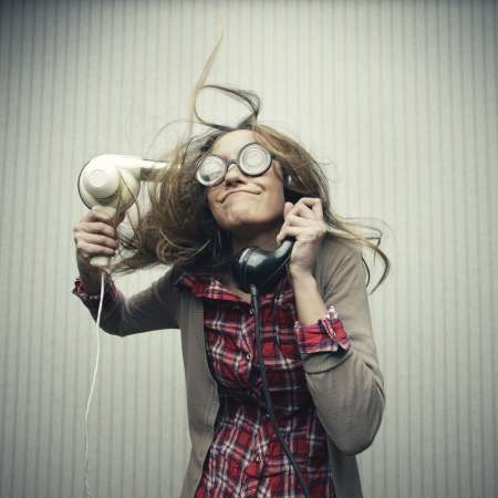 crazy girl: Nerdy woman using hair drayer and talking retro vintage black telephone