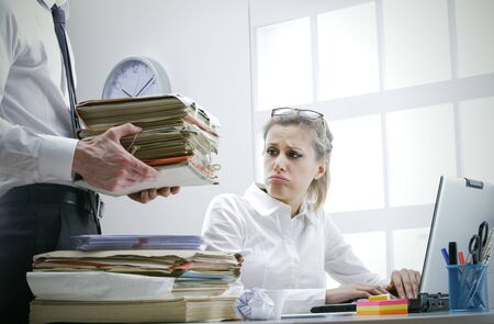 woman hard working: Stressed businesswoman with a too much paperwork and documents Stock Photo