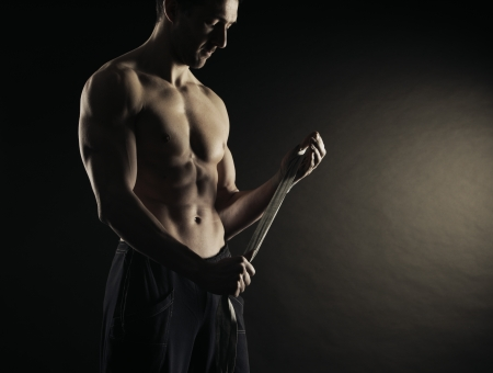 strongman: Muscular man boxer wearing white strap on wrist